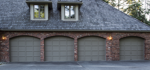 Four car garage doors made of wood and brick